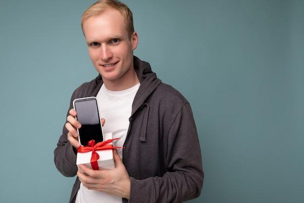 Крупным планом портретная фотография крутого красивого счастливого молодого человека в сером свитере и белой футболке, стоящего изолированно на синем фоне стены, держащего смартфон и показывающего телефон с дисплеем пустого экрана