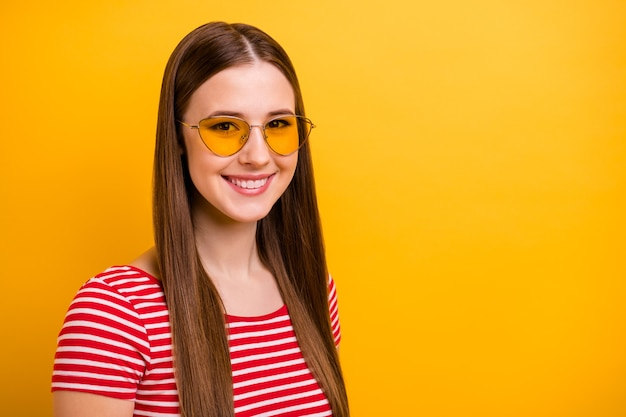 Closeup portrait photo of pretty charming young girl white teeth smile empty space free time spend day off wear sun specs striped white red shirt vivid yellow color background