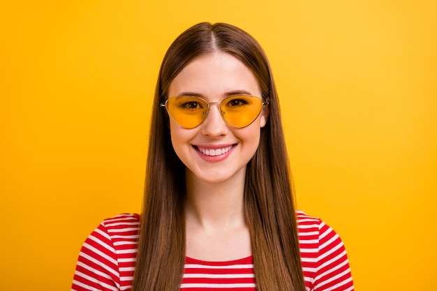 Closeup portrait photo of stunning careless young girl long hairstyle genuine smile enjoying summer weekend wear sun specs striped white red shirt bright yellow color background