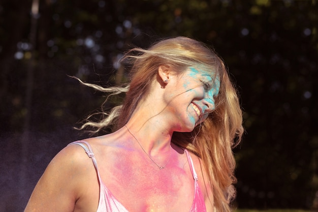 Closeup portrait of positive blonde woman with wind in hair posing on holi festival