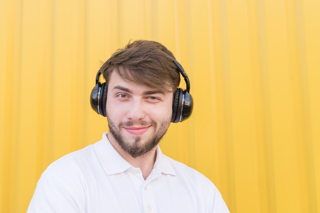 Closeup portrait of a positive young man with headphones on the head while listening to music.
