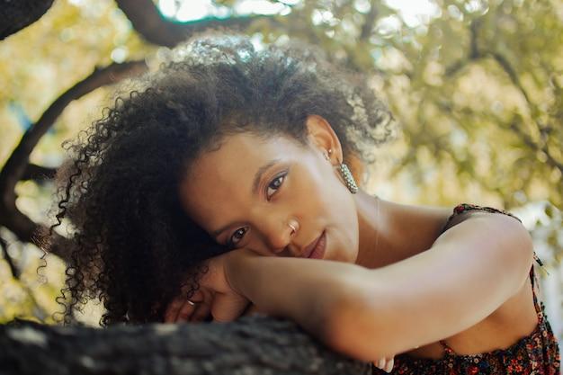 Closeup ritratto di una bella donna afro-colombiana appoggiata su una superficie di pietra all'aperto in un parco a