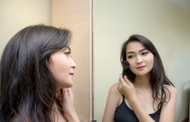 Closeup portrait a pretty asian woman at the mirror applying cosmetic paint brush