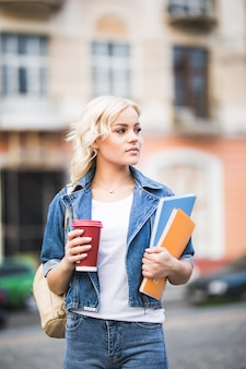 Closeup portrait of pretty blonde girl student with a lot of notebooks dressed up in jeans