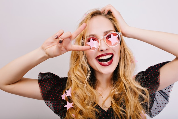 Closeup portrait of pretty blonde with curly hair enjoying time at party, celebrating, showing peace, smiling. she wearing black nice dress, pink glasses.