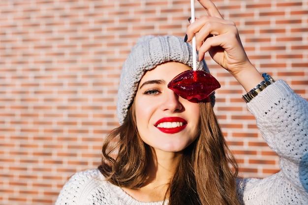 Ragazza graziosa del ritratto del primo piano con capelli lunghi in cappello lavorato a maglia divertendosi con le labbra rosse della lecca-lecca sulla parete.