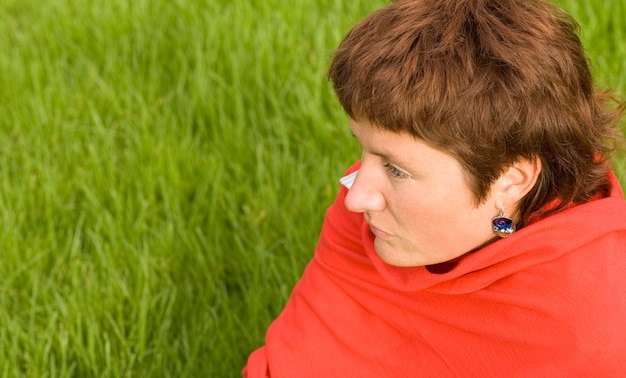 Closeup portrait of pretty redhead woman sitting on the grass