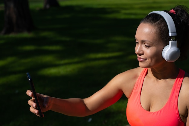 Closeup portrait of pretty woman with headphones holding a smartphone while relaxing after running
