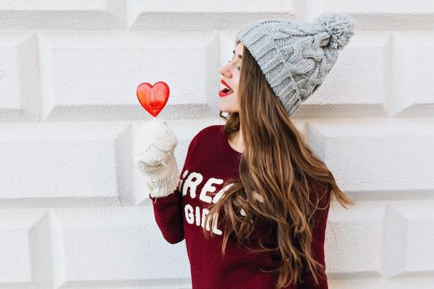 Ragazza graziosa del ritratto del primo piano in maglione marsala e cappello lavorato a maglia sul muro grigio. ha guanti bianchi, guardando il lecca-lecca cuore rosso in mano.