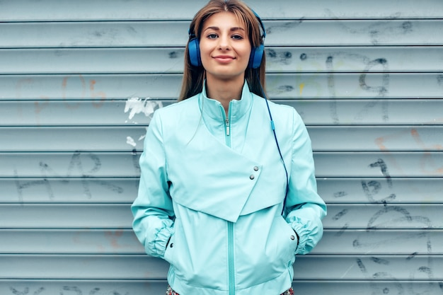 Closeup portrait of pretty young woman smiling and listening music standing on the street with earphones