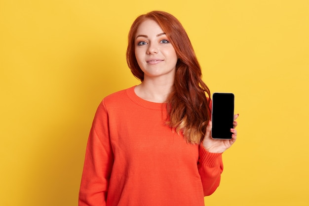 Closeup portrait of red haired female holding smart phone with black screen in hands