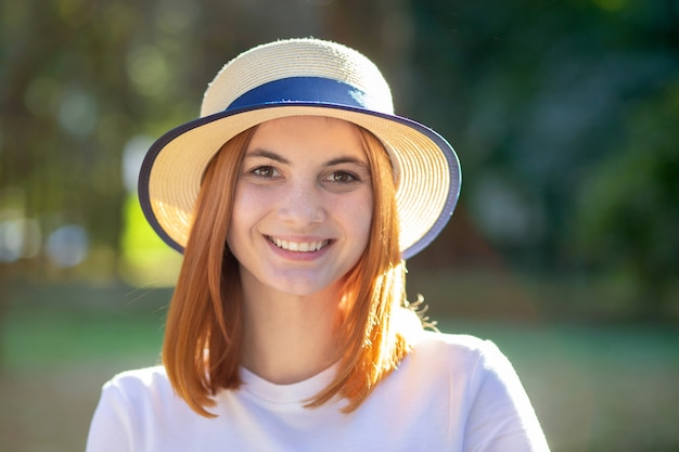 Closeup portrait of redhead hipster teenage girl in yellow hat smiling outdoors in sunny summer park.