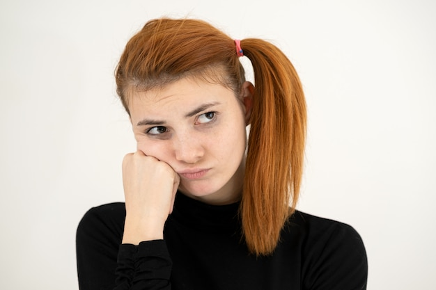 Closeup portrait of a sad redhead teenage girl with childish hairstyle looking offended isolated on white backround.