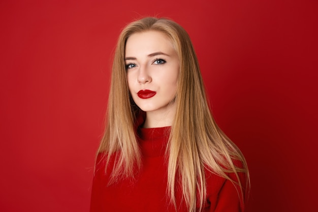 Closeup portrait of seductive blonde woman against a red background