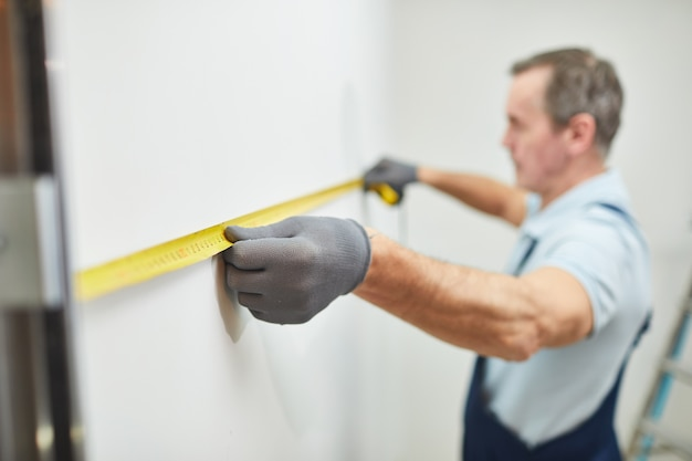 Closeup portrait of senior construction worker measuring wall while renovating house, copy space