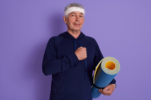 Closeup portrait of senior dresses blue hoody and white head band, keeping fist on his chest, holding yoga mat in hands, being photographed after physical exercise