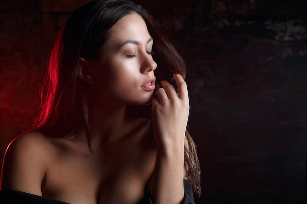Closeup portrait of sexy girl with naked shoulders, posing with red light at studio. space for text