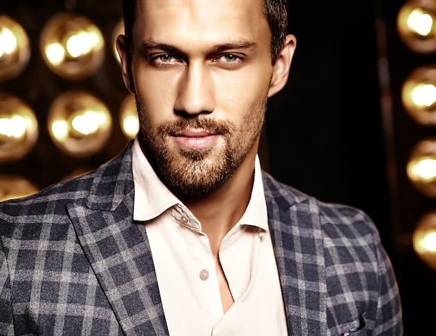 Closeup portrait of sexy handsome fashion male model man dressed in elegant suit on black studio lights background