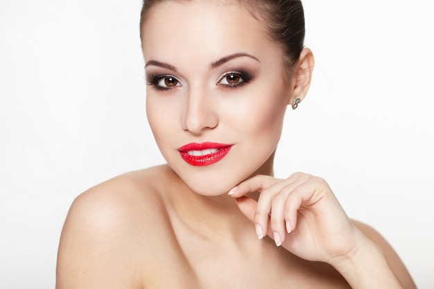 Ritratto del primo piano del modello di giovane donna caucasica sorridente sexy con labbra rosse glamour, trucco luminoso, trucco della freccia dell'occhio, carnagione di purezza. pelle pulita e perfetta denti bianchi