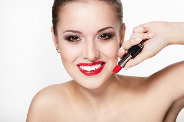 Ritratto del primo piano del modello sexy sorridente giovane donna caucasica con labbra rosse glamour, trucco luminoso, trucco della freccia dell'occhio, carnagione di purezza con rossetto rosso. pelle pulita e perfetta denti bianchi