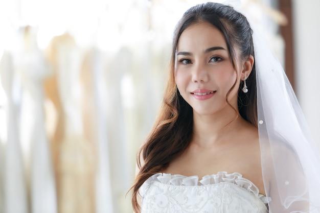 하얀 웨딩 드레스를 입은 아시아 젊고 아름다운 행복한 긴 머리 신부의 클로즈업 초상화는 흐릿한 배경의 드레스로 가득 찬 탈의실에서 카메라를 보고 웃고 있습니다.