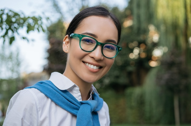 Closeup portrait of smiling asian student wearing eyeglasses looking at camera outdoors, education concept