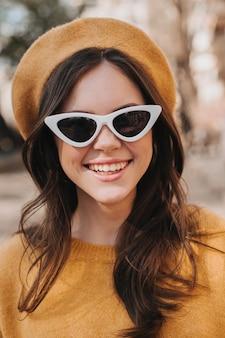 Closeup ritratto di ragazza sorridente in berretto giallo e occhiali da sole. giovane donna castana in maglione arancione che ride mentre cammina