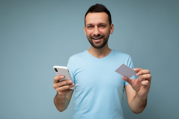 Closeup portrait of smiling handsome man wearing everyday clothes isolated on background wall holding and using phone and credit card making payment looking at camera.