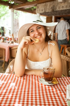 Closeup portrait of smiling woman eating cookie and drinking tea at cafe