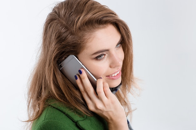 Closeup portrait of a smiling young woman talking on the phone isolated on a white background