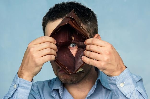 클로 우즈 업 초상화, 스트레스, 화가, 슬프고 불행 한 젊은 남자와 함께 서 있는 빈 지갑의 구멍을 찾고. 재정적 어려움, 나쁜 경제 개념. 부정적인 감정