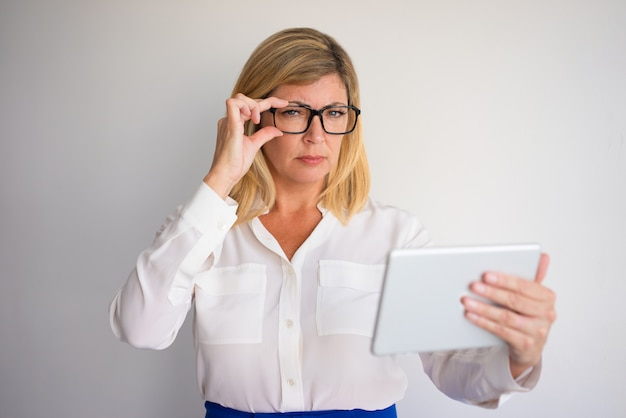 Closeup portrait of strict attractive fair-haired woman adjusting glasses