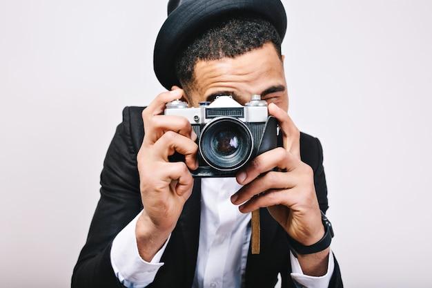 Tirante alla moda del ritratto del primo piano in cappello, vestito che fa foto sulla macchina fotografica. turista felice, divertirsi, gioia, isolato, sorridere, esprimere positività, umore allegro, fotografo.