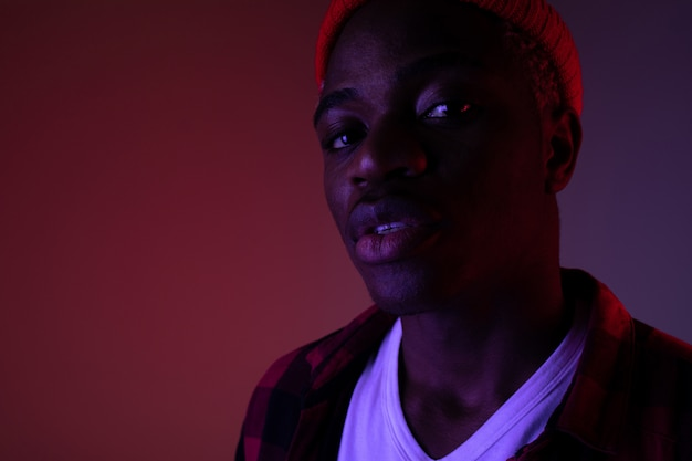 Closeup portrait of a stylish handsome black man looking at the camera in neon light in the shade