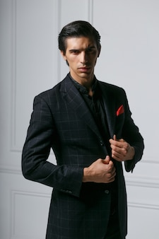 Closeup portrait of stylish young man in black suit with red silk scarf in pocket, over grey background.