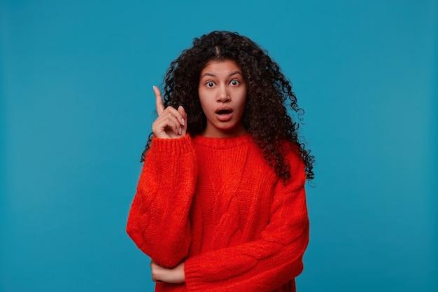 Портрет крупным планом удивил молодую кудрявую женщину, указывая указательным пальцем вверх и держа рот открытым, изолированную синюю стену