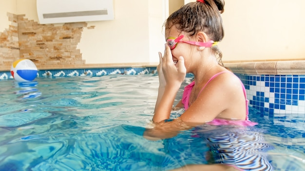 Closeup portrait of teenage girl wearing goggles before swimming in the pool
