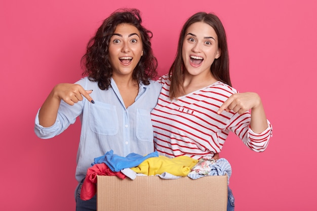 Closeup portrait of two excited girls pointing at carton box with clothes for secondary using