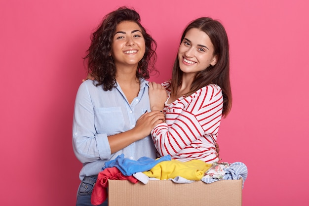 Closeup portrait of two excited girls with carton box full of clothes for secondary using