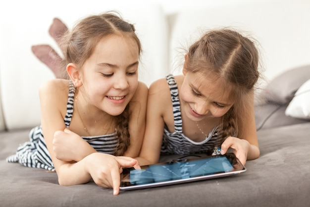 Closeup portrait of two smiling girls lying on couch and using tablet