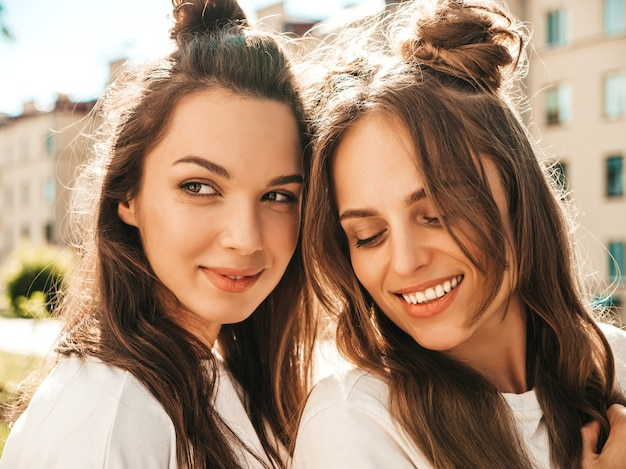 Closeup portrait of two young beautiful smiling hipster female in trendy summer white t-shirt clothes