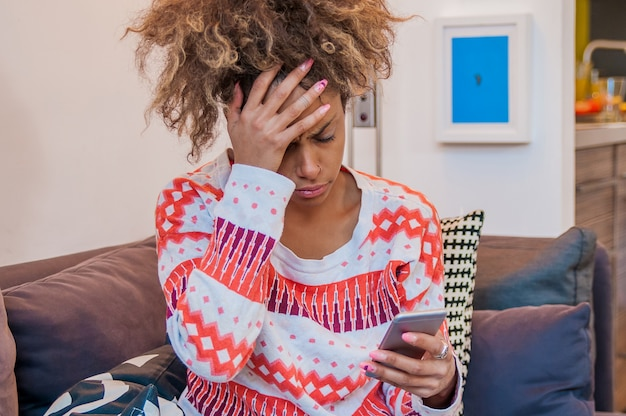 クローズアップ、肖像画、悲しい、懐疑的、不幸、深刻なアフリカの女性は電話で話す。否定的な人間の感情の表情の感情、生活の反応。悪いニュース