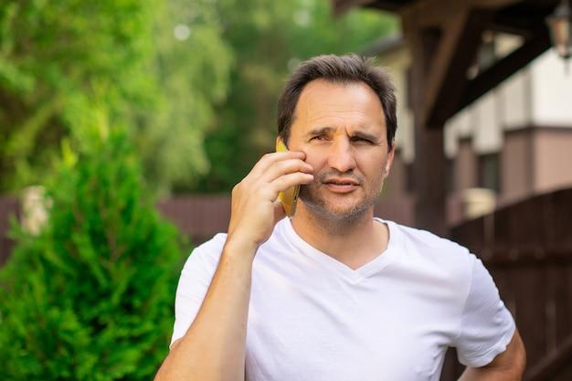 흐린 녹색 자연, 가로 그림에 야외 휴대 전화에 말하는 흰색 티셔츠에 한 잘 생긴 형태가 이루어지지 않은 곁눈질 40 대 남자의 클로 우즈 업 초상화보기. 평정의 개념