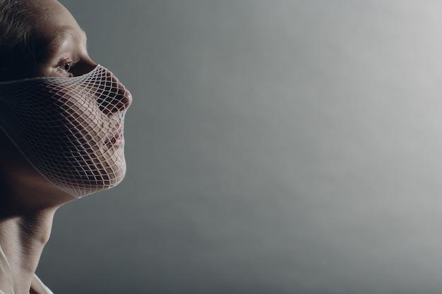 Closeup portrait of white caucasian albino blond woman fashion model wearing quarantine medical face mask coarse mesh net on grey background. covid-19 coronavirus protection concept
