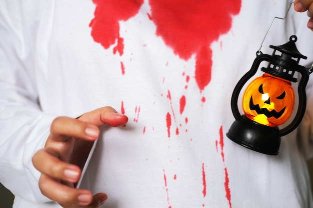 Closeup portrait of white clothes covered with blood and hand holding pumpkin lantern