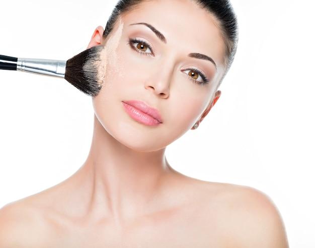 Ritratto del primo piano di una donna che applica il fondotinta tonale cosmetico asciutto sul viso utilizzando un pennello da trucco.