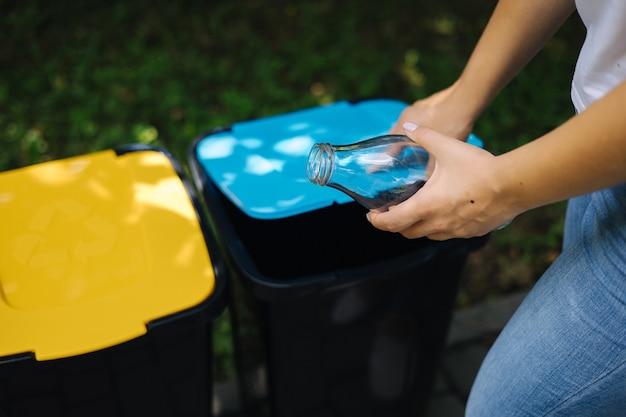 Крупным планом портрет женщины рука бросает пустую стеклянную бутылку в мусорное ведро разного цвета из пластика