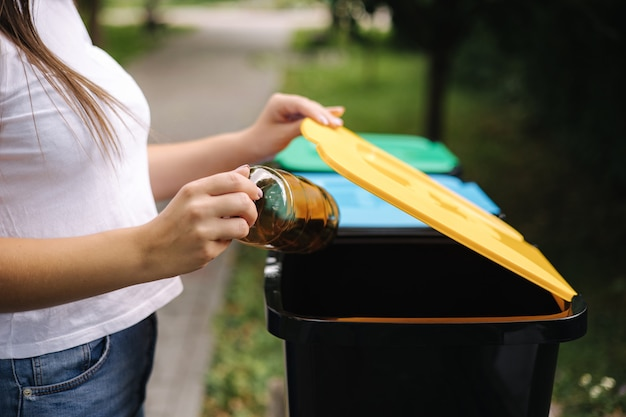 Крупным планом портрет женщины рука бросает пустую пластиковую бутылку с водой в мусорное ведро