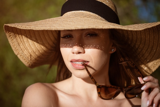 Closeup portrait of a woman in a hat from the sun on a summer sunny day beautiful caucasian young wo...
