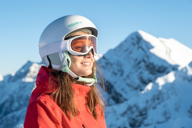 Closeup portrait of woman in helmet and mask with on ski resort